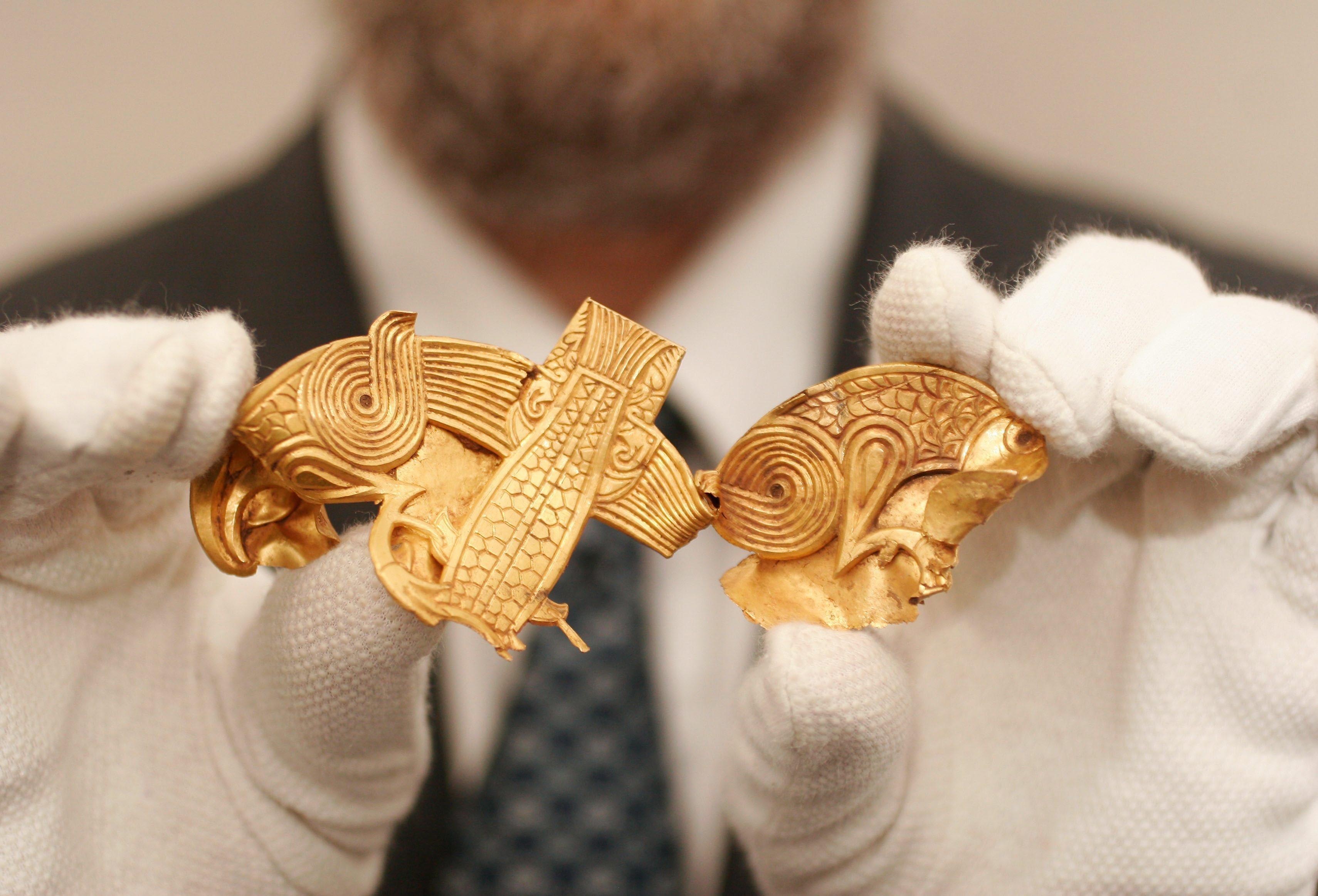 Una placa de oro con dos águilas separadas por peces en el tesoro de Staffordshire