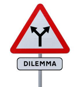 Una señal de tráfico que muestra dos flechas que conducen en diferentes direcciones y una etiqueta debajo que dice dilema