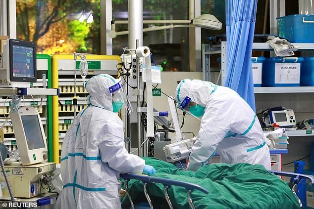 La esposa, de 60 años, había viajado a Wuhan, donde se originó el virus, a fines de diciembre para cuidar a su padre anciano. En la imagen: el personal médico con trajes de protección trata a un paciente con coronavirus en el Hospital Zhongnan de Wuhan, el 28 de enero