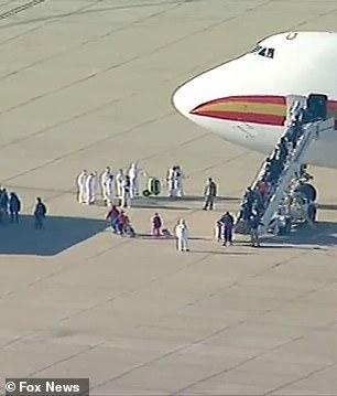 Los funcionarios en trajes de materiales peligrosos se encontraron con los pasajeros cuando se bajaban del avión y subían a los autobuses en espera