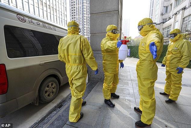 Varios países han desaconsejado los viajes no esenciales a China. En la imagen: los trabajadores funerarios se desinfectan después de manejar a una víctima de coronavirus en Wuhan el jueves