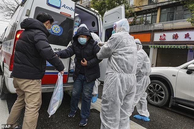 Los trabajadores médicos con equipo de protección ayudan a un paciente sospechoso de coronavirus a salir de una ambulancia en Wuhan