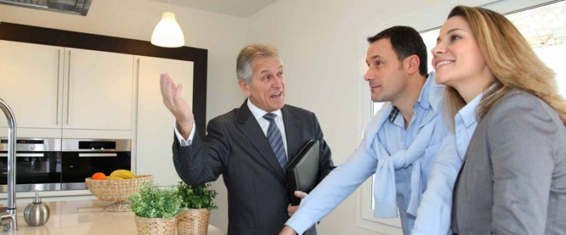 Agente inmobiliario que muestra la casa moderna a la pareja