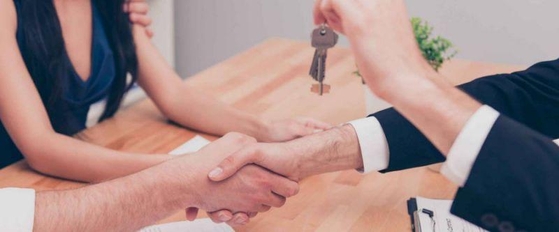Foto de primer plano del apretón de manos. Broker dando las llaves de la nueva casa