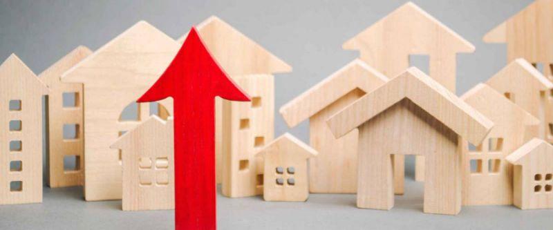 Flecha roja hacia arriba y casas de madera en miniatura. El concepto de aumento de los precios de la vivienda.