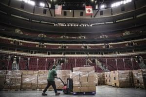 En esta foto del 20 de marzo de 2020 proporcionada por United Center, un trabajador mueve la comida al piso del United Center. en Chicago. El Gran Depósito de Alimentos de Chicago, el banco de alimentos de Chicago, utilizará el United Center como una instalación de almacenamiento satelital en respuesta a la mayor necesidad de alimentos durante la pandemia de coronavirus.