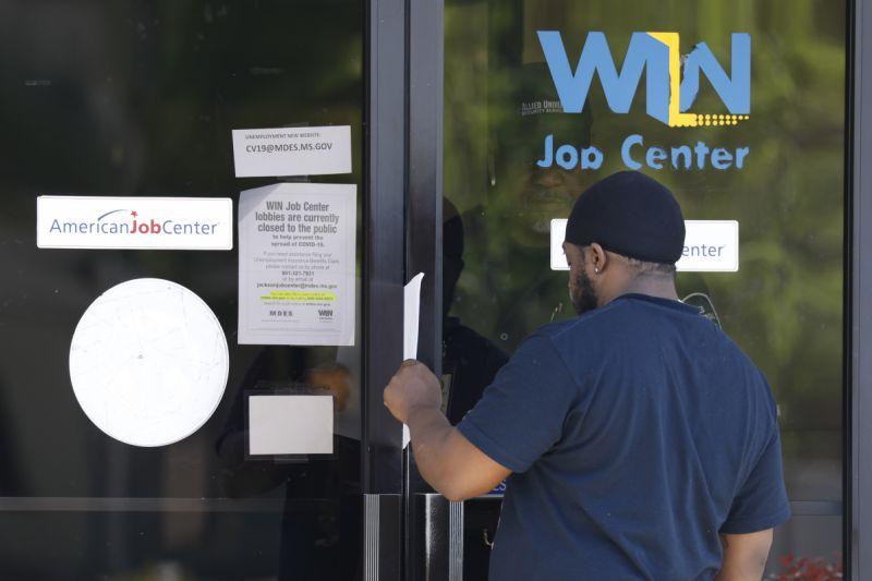 Tyrone Keoton Jr., recibe un formulario de solicitud de beneficios de desempleo por un guardia de seguridad detrás de las puertas de vidrio de este Centro de Empleo WIN en el norte de Jackson, Miss., Jueves 2 de abril, 2020. Los vestíbulos de los centros de trabajo están cerrados en todo el estado para evitar la propagación de COVID-19. La agencia alienta a los residentes a solicitar sus beneficios en línea, sin embargo, el gran número de solicitantes ha enfatizado el sistema. Los centros de trabajo locales están poniendo a disposición solicitudes de desempleo en papel y los solicitantes las están llenando y empujando hacia atrás a través de las ranuras o puertas de correo tan bien como pueden. (AP Photo / Rogelio V. Solis)